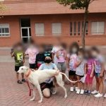A group of children posing with the galgo