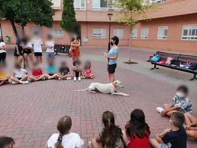 Jisseth talking to a group of children while the galgo lies quietly